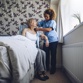 person with dementia sitting at side of bed getting help from a home health aide